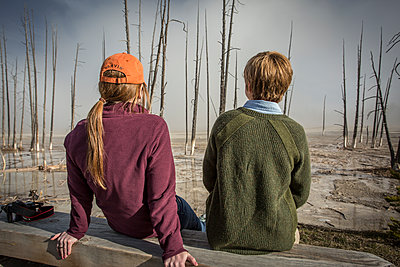 Two women relax while watching geysers in Yellowstone. - p343m1111897 by Jess McGlothlin Media