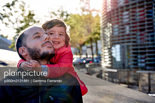 Two-year-old girl hugging her father in the city in winter. Barcelona, Spain - p300m2131881 by Gemma Ferrando