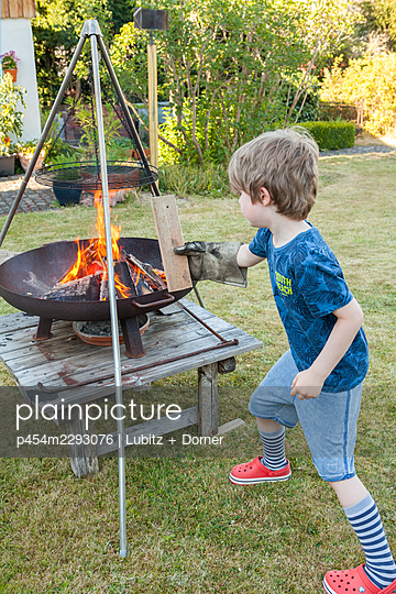 Stoking a fire with wood carefully - p454m2293076 by Lubitz + Dorner