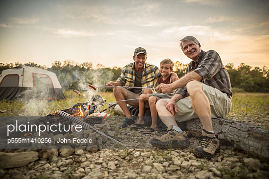 Three generations of Caucasian men roasting hot dogs over campfire - p555m1410256 by John Fedele