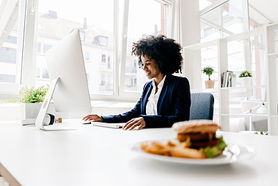 Young businesswoman working with hamburger on her desk - p300m1460694 by Kniel Synnatzschke
