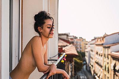 Beautiful barechested young woman on balcony above the city - p300m2042230 von Kike Arnaiz