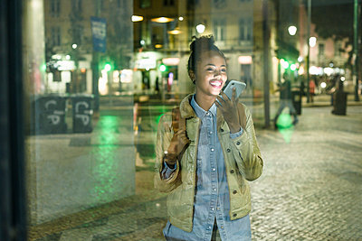 Portrait of young woman on the phone in the city by night, Lisbon, Portugal - p300m2144558 by Uwe Umstätter