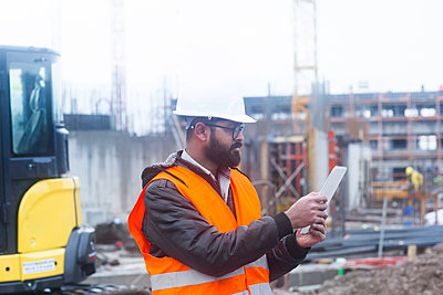 Construction engineer wearing hard hat and safety vest usimng tablet at construction site - p300m2160299 by Sigrid Gombert