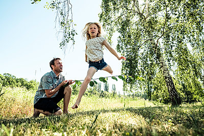 Father with daughter jumping over stick in poppy meadow - p300m2160741 von Wilfried Feder