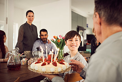 Smiling boy looking at grandfather holding birthday cake with family in party - p426m1580212 by Maskot