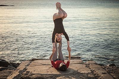 Women practising acro yoga at seaside - p429m2090680 by ROBERTO PERI