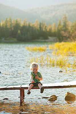Caucasian boy sitting on wooden deck over lake - p555m1411547 by John Lee