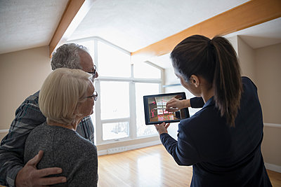 Interior designer with digital tablet showing senior couple augmented reality, planning living room remodel - p1192m1559993 by Hero Images