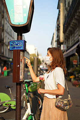 A woman wearing a cloth mask at the bus stop - p1610m2208788 by myriam tirler