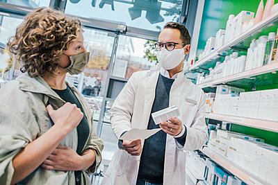 Pharmacist recommending medicine to smiling customer in chemist shop - p300m2243197 by Mareen Fischinger