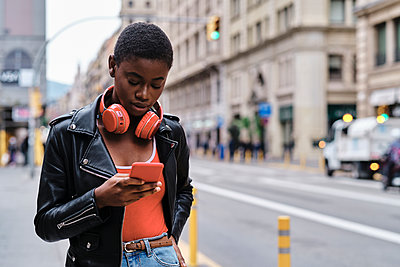 Young woman with headphones using smart phone while standing in city - p300m2250154 by Alvaro Gonzalez