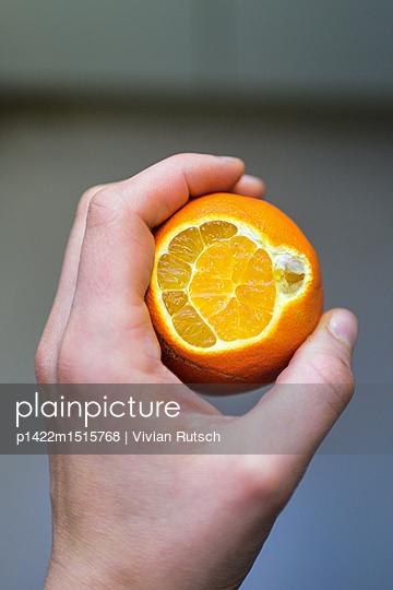 Hand hält eine aufgeschnitte Orangehttps://photobay.plainpicture.com/submissions/51259/indexings/new?indexing=incomplete# - p1422m1515768 von Vivian Rutsch