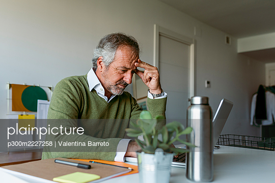 Mature man worried while working on laptop at home - p300m2227258 by Valentina Barreto
