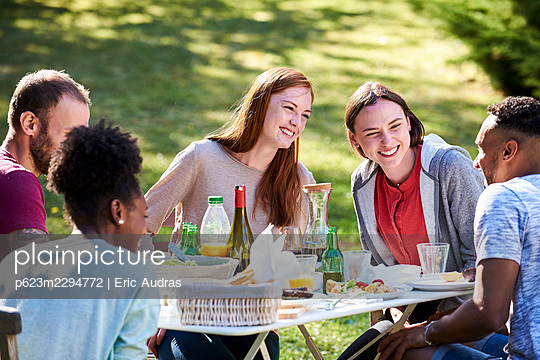 Smiling young friends having enjoying food in park - p623m2294772 by Eric Audras