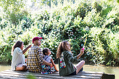 Family blowing bubbles on dock in woods - p1023m2066683 by Sam Edwards