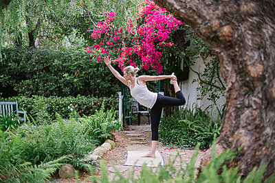Blond woman doing yoga in a garden. - p1100m1080229 by Mint Images