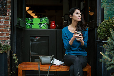 Thoughtful woman holding disposable glass while sitting on bench outside coffee shop - p1166m1144718 by Cavan Images
