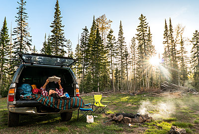 Good Spot to Read - Young woman reading wile car camping in forest - p1166m2078432 by Cavan Images