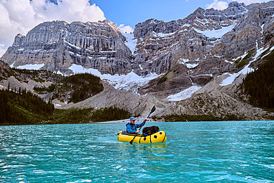 Adventure photographer paddles pack raft across Cirque Lake in Banff. - p1166m2153624 by Cavan Images