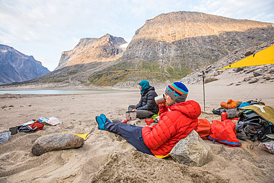 Mountaineers relax on a sunny day at basecamp, Baffin Island - p1166m2261222 by Cavan Images