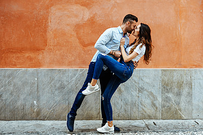 Affectionate couple in love kissing in front of a wall outdoors - p300m2012646 by Javier Sánchez Mingorance