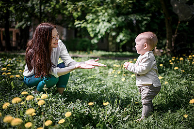 Mother with her baby boy on a meadow in the park - p300m2139840 by Ekaterina Yakunina