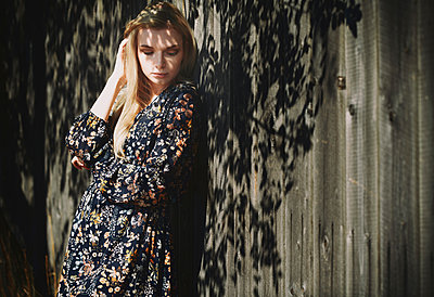 Beautiful woman with hand in hair leaning on wooden wall - p300m2250362 by Arman Zhenikeyev
