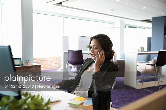 Mid adult businesswoman on cell phone in open plan office - p1192m2123340 by Hero Images