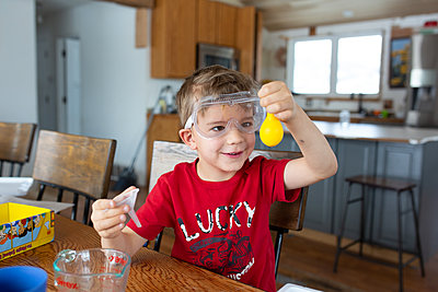 Boy holding up yellow balloon during science experiment at home - p1166m2269668 by Cavan Images