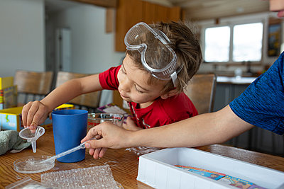 Children working with chemistry set at table - p1166m2269670 by Cavan Images