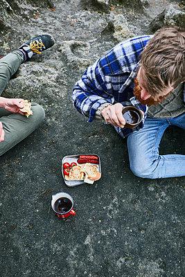 Men having snack on rock - p1573m2175255 by Christian Bendel