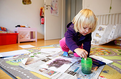 Little girl painting with watercolours on the floor of children's room - p300m1189490 by Hans Lippert