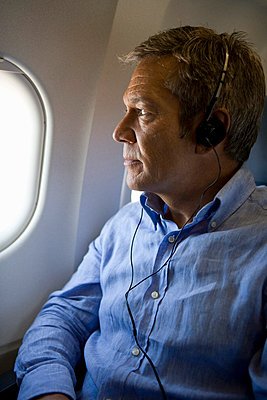A male passenger listening to headphones and looking out the window of a plane - p3018305f by Halfdark