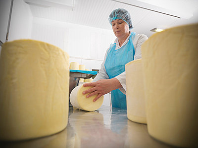 Worker wrapping cheese in factory - p42916440f by Monty Rakusen