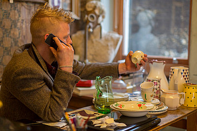 Man talking on cell phone at table - p429m767862 by dotdotred