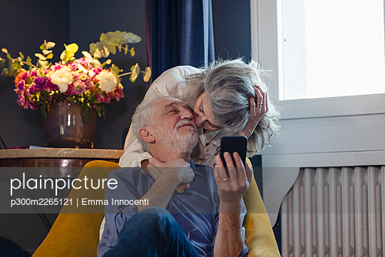Affectionate woman kissing man while standing behind at home - p300m2265121 by Emma Innocenti
