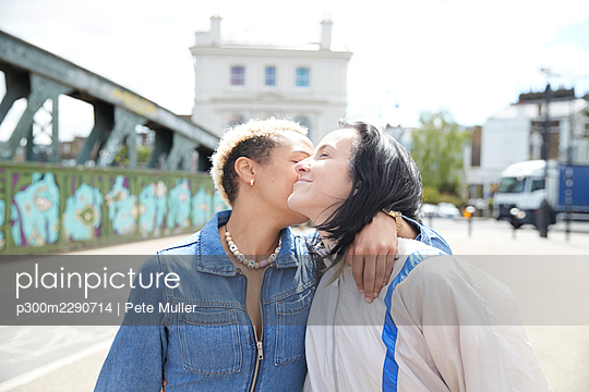 Lesbian woman kissing girlfriend during sunny day - p300m2290714 by Pete Muller