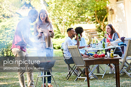 Young man preparing food in barbecue by his friends sitting at table - p623m2294762 by Eric Audras