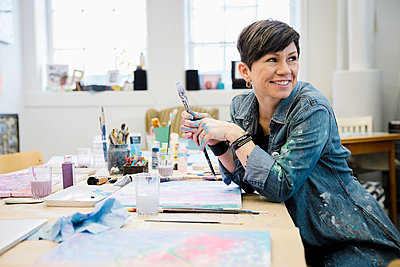 Smiling female artist painting in studio - p1192m2066773 by Hero Images