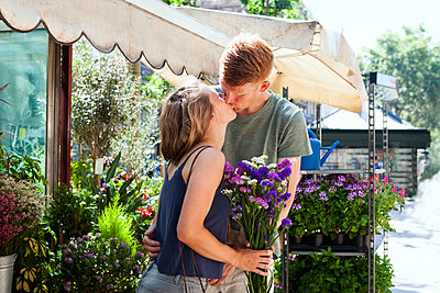 Kissing couple in front of flower stall - p300m1157303 by Valentina Barreto