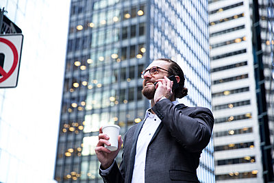 Happy young businessman with coffee to go on the phone, New York City, USA - p300m2114683 by Michelle Fraikin