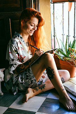 Red-haired tattooed woman at home writing in a notebook near the window - p300m2132002 by Javier Sánchez Mingorance