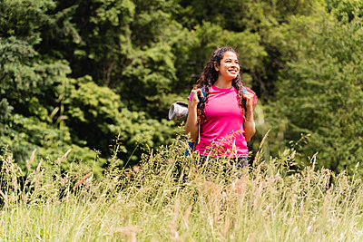Smiling female hiker with backpack looking away while hiking in meadow - p300m2290537 by Francesco Morandini