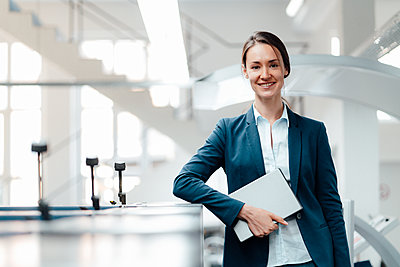Businesswoman with digital tablet standing at workshop - p300m2300283 by Kniel Synnatzschke