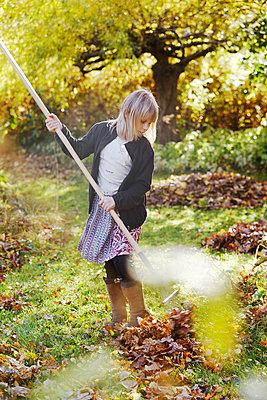 Girl raking leaves in garden - p312m1522145 by Anna Kern