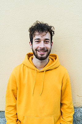 Young man in yellow hoody standing in front of wall, portrait - p429m2091301 by Garage Island Crew
