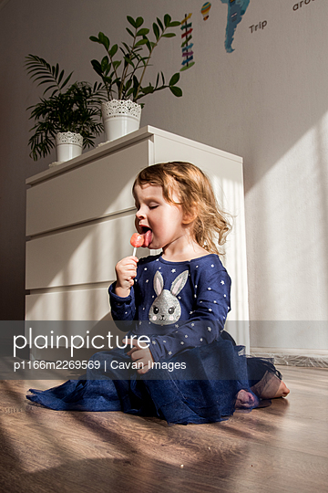 the girl is sitting on the floor and eating candy on a stick - p1166m2269569 by Cavan Images