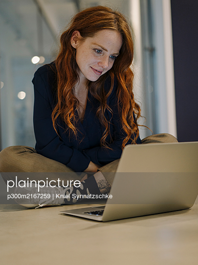 Redheaded woman using laptop on the floor - p300m2167259 by Kniel Synnatzschke