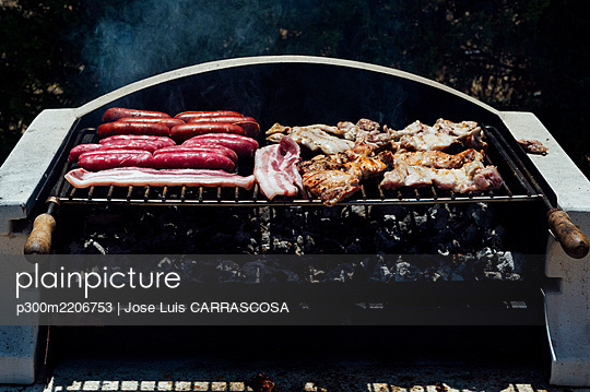 Close-up of meat on barbecue grill in yard - p300m2206753 by Jose Luis CARRASCOSA